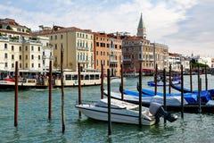 Venecia, Italia Barco de motor y góndolas parqueados cerca de los posts de madera Fotografía de archivo libre de regalías