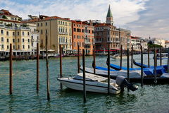 Venecia, Italia Barco de motor y góndolas parqueados cerca de los posts de madera Imagenes de archivo
