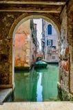 Venecia, Italia: canal veneciano con un barco en el agua verde imagenes de archivo