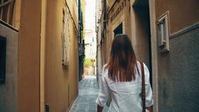 VENECIA, ITALIA - 8 DE AGOSTO DE 2017 Mujer joven que camina a lo largo de la calle peatonal estrecha cerca de tienda de la moda  almacen de metraje de vídeo