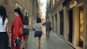 VENECIA, ITALIA - 8 DE AGOSTO DE 2017 Mujeres jovenes que caminan a lo largo de tiendas de la moda en un lugar turístico metrajes