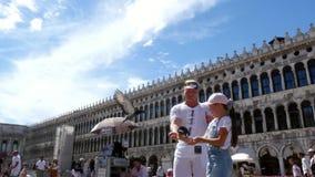 Venecia, Italia - 7 de julio de 2018: la opinión la muchacha feliz del hombre y del niño, turistas, sosteniendo las palomas, alim almacen de metraje de vídeo