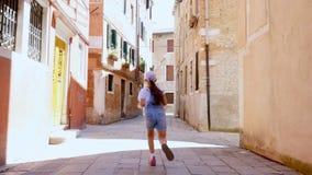 VENECIA, ITALIA - 7 DE JULIO DE 2018: a lo largo de una calle estrecha de Venecia, entre las casas viejas, una muchacha del adole almacen de video