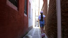 VENECIA, ITALIA - 7 DE JULIO DE 2018: a lo largo de una calle estrecha de Venecia, entre las casas viejas, una muchacha del adole almacen de metraje de vídeo