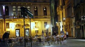 VENECIA, ITALIA - 7 DE JULIO DE 2018: opiniones de la noche de Venecia En el cuadrado, los turistas se sientan en las tablas de u almacen de video