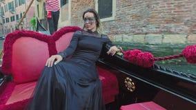 VENECIA, ITALIA - 19 DE JUNIO DE 2016: Mujer hermosa en vestido negro con el montar a caballo carnaval de la máscara en la góndol almacen de video