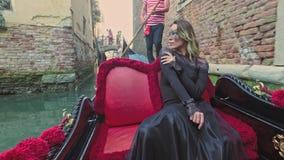 VENECIA, ITALIA - 19 DE JUNIO DE 2016: Mujer hermosa en vestido negro con el montar a caballo carnaval de la máscara en la góndol almacen de metraje de vídeo