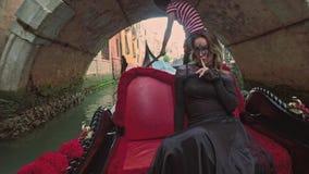 VENECIA, ITALIA - 19 DE JUNIO DE 2016: Mujer hermosa en vestido negro con el montar a caballo carnaval de la máscara en la góndol metrajes