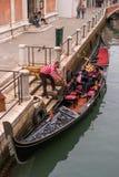 Venecia, Italia - 13 de octubre de 2017: El gondolero ayuda a la red de los pasajeros en la góndola La góndola se adorna rico Imagen de archivo