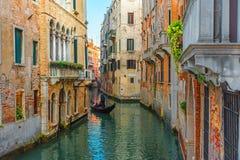 Venecia, Italia Gondolero veneciano que flota en la góndola con los turistas a través de las aguas verdes del canal de Venecia fotos de archivo
