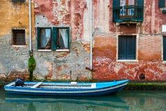 Venedig cityscape, fartyg på den smala vattenkanalen nära den färgrika väggen med fönster Fotografering för Bildbyråer