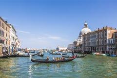 Venedig, den storslagna kanalen, domkyrkan av Santa Maria della Salute och gondoler med turister Royaltyfri Foto