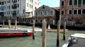 Venedig Det äldre mananseendet i motorbåt rider över kanalen stock video