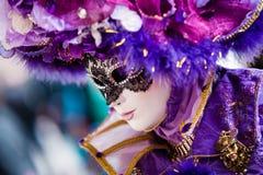 VENEDIG FEBRUARI 10: En oidentifierad kvinna i typisk färgrik klänning poserar under den traditionella Venedig karnevalet Arkivfoton