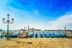 Venedig, gatalampa och gondoler eller gondole och kyrka på bakgrund. Italien Arkivbilder