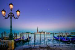 Venedig, gatalampa och gondoler eller gondole på solnedgång och kyrka på bakgrund. Italien Arkivbild