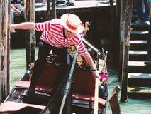 Venedig gondoljär som försöker att hålla jämvikt på gondolfartyget Fotografering för Bildbyråer