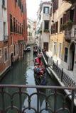 Venedig gondoljär som svävar på en traditionell venetian kanal Arkivbilder
