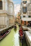 VENEDIG ITALIEN April 13, 2015: Härlig stadssikt och typisk gondol på den smala venetian kanalen, Venedig, Italien Tonad fyrkanti Royaltyfri Bild