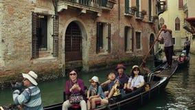 VENEDIG ITALIEN - AUGUSTI 8, 2017 Asiatisk familj som tar en ritt på en berömd Venetian gondol arkivfilmer