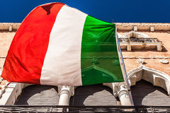 VENEDIG ITALIEN - AUGUSTI 20, 2016: Italiensk flagga och fasader av den gamla medeltida byggnadsnärbilden på Augusti 20, 2016 i V Arkivfoton