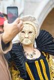 Venedig Italien - 23 02 2019: Den härliga maskeringen och mannen tar ett foto på mobiltelefonen på den St Mark fyrkanten under ka arkivfoton