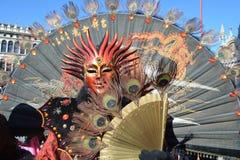 VENEDIG ITALIEN FEBRUARI 23: En oidentifierad man klär i maskering med den stora utarbetade orientaliska fanen Arkivfoto