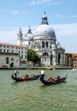 Venedig Italien - gondoler för 15 Juni 2017 - två med folk som tycker om deras Tid i Venedig och basilika av St Mary av hälsa i Arkivbilder
