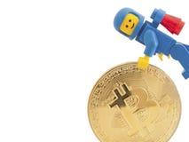 Venedig Italien - Januari 07, 2018: En astronaut som det Lego diagramet anseende bredvid Bitcoin mynt, Januari 07, 2018 i Venedig Royaltyfri Bild