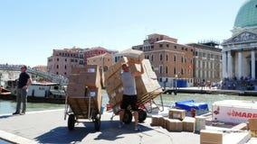 VENEDIG ITALIEN - JULI 7, 2018: arbetare lastar av packeleveransfartyget som är fullt av askar, jordlotter Det post- fartyget lev lager videofilmer