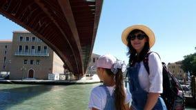Venedig Italien - Juli 7, 2018: på en varm sommardag, turister, kvinna i hatt och solglasögon och engammal flicka lager videofilmer