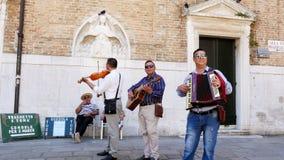 Venedig, Italien - 7. Juli 2018: Straßenmusiker, das Trio, spielend auf der Straße von Venedig, unterhält Touristen stock video
