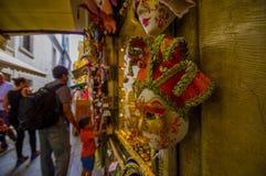 VENEDIG ITALIEN - JUNI 18, 2015: Den röda och guld- härliga maskeringen i en souvenir shoppar i Venedig, selektiv fokus Turists Arkivbilder