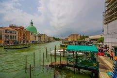 VENEDIG ITALIEN - JUNI 18, 2015: Goldola port för turists i den Venetian kanalen, vatten kör lite varstans staden Green Dome Arkivbilder