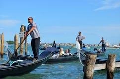 VENEDIG, ITALIEN - 20. Juni 2015: Gondolieri und ihre Passagiere Lizenzfreies Stockbild