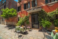 VENEDIG ITALIEN - JUNI 15, 2016 trevlig sikt med några tabeller av gatakafét i Venedig royaltyfri bild