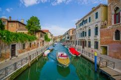 VENEDIG, ITALIEN - 18. JUNI 2015: Venedig-Kanal mit verschiedenen Booten auf den Seiten und den nicht identifizierten Männern, di Lizenzfreie Stockfotos