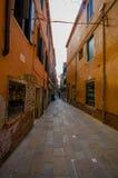 VENEDIG ITALIEN - JUNI 18, 2015: Venedig smala gator i en pinturesqueneigborhood, folk som shoppar på sidorna och Arkivbild