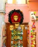 Venedig Italien - Maj 10, 2014: Venetian karnevalmaskeringar, souvenir shoppar på en gata Royaltyfria Bilder