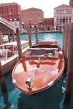 Venedig, Italien am 28. November 2018: Helle rote hölzerne Yacht festgemacht auf Kanal mit altem Gebäude auf der Bank lizenzfreie stockfotografie