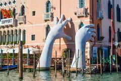 VENEDIG ITALIEN - SEPTEMBER, 2017: Monumentala stora händer stiger från vattnet i Venedig för att markera klimatförändring med bl royaltyfri bild