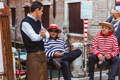 VENEDIG, ITALIEN - 22. SEPTEMBER 2017: Zwei Gondolieri in den traditionellen Kostümen auf der Brücke während einer Ruhepause lizenzfreie stockfotografie