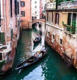 Venedig kanal med gondoljärer och färgrika byggnader royaltyfri foto