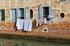 Venedig kanal med tvätteriuttorkning i solen Arkivfoto