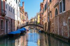 Venedig-Kanal mit Brücke und alten Backsteinbauten Verankerte Boote Stockbild