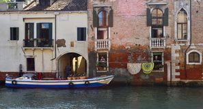 Venedig-Kanal mit Lieferungsboot und -leuten an den Fenstern Stockfotos