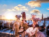 Venedig med karnevalmaskeringar mot färgrik soluppgång i Italien Royaltyfri Bild