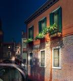 Venedig nattsikt med huset och den lilla bron Arkivbild