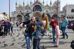 Venedig - Oktober 04: Okända kvinnliga turister har gyckel med duvor på piazza San Marco på Oktober 04, 2017 i Venedig Arkivbild