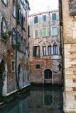 Venedig sikt av en kanal mellan tegelstenhus arkivbilder